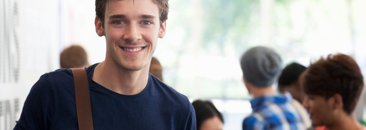 Portrait of smiling university student standing in corridor during break, people in background talking